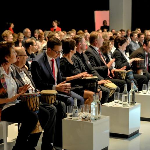 Aliud Pharma: Das Publikum in der ersten Reihe hat Trommeln in den Händen und trommelt.