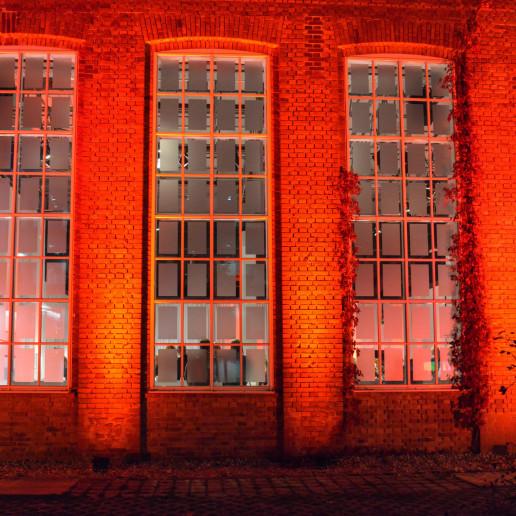 Aliud Pharma: Altes Backsteingebäude mit großen Fensterfronten in rot beleuchtet.