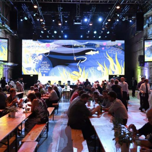 Baader 100 Jahre: Die Gäste sitzen an Biertischen, im Hintergrung ist die Bühne mit einer großen Leinwand und jeweils einer kleineren Leinwand links und rechts.