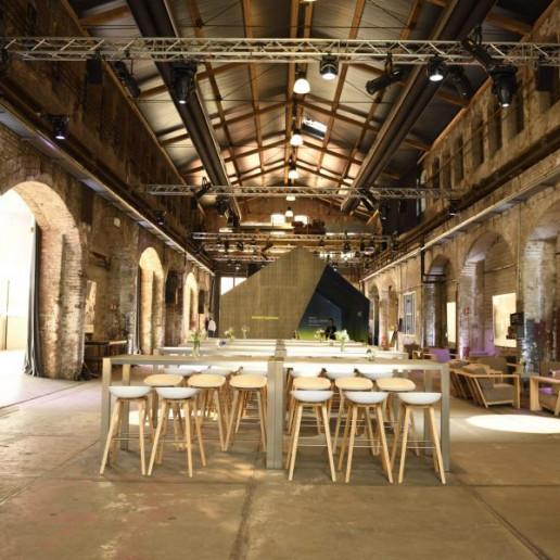 Baader 100 Jahre: In mitten einer alten Fabrikhalle stehen graue Stehtische mit Barhockern.