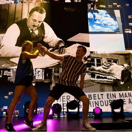 Baader 100 Jahre: zwei Tänzer auf der Bühne. im Hintergrund sind große Bilder aus den sechsziger Jahren auf der Leinwand