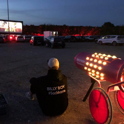 Billy Boy Autokino: Der Promoter sitz neben der beleuchteten Sackkarre auf dem Boden und guckt ein Film im Autokino.