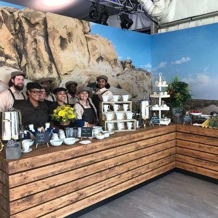 BMW Group: Hinter einer Bar aus Holz steht das Personal vom Catering.Auf der Bar stehen Kaffeetassen und Obst.