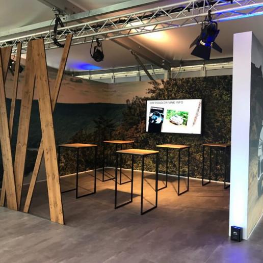 BMW Group: In einem abgetrennten Teil des Zeltes stehen Stehtische mit einer Holzplatte. An der Wand hängt ein TV auf dem man Offroad Driving Infos bekommt.