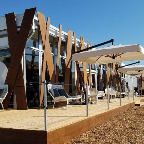 BMW Group: Blick auf die Terrasse von der Seite. Auf der Terrasse stehe Sitzmöglichkeiten und große Schirme.