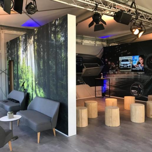 BMW Group: auf der rechten Seite ist eine Tagunssituation, in der die Gäste auf abgesägten Baumstämmen sitzen und links ist eine Lounge, in der man auf grauen Sofas sitzt.