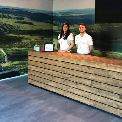 BMW Group: Zwei Promoter stehen hinter einem großen Tresen aus Holz, an dem man sich registrieren kann.