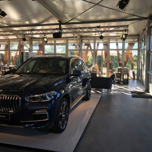 BMW Group: Im Zelt steht ein neuer BMW X 5 auf einem Podest. Im Hintergrund gibt es Sitzmöglichkeiten.