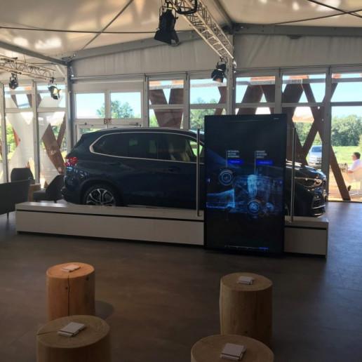 BMW Group: Im inneren des Zeltest steht ein BMW X5, auf einem Display vor dem Auto wird das Getriebe erklärt.