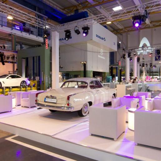 Daimler 75 Jahre PKW: Weiße Ledersessel mit Beistelltisch auf einem Podest. Im Hintergrund steht ein weißer Borgward.