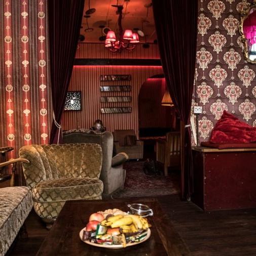 Daimler AG Leadership Nights: Blick in eine alte Kneipe mit alten Samt Sofas und alten Tischen auf denen ein Obstkorb steht.