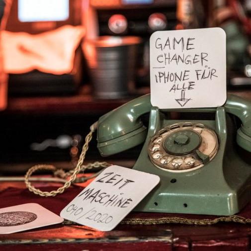 Daimler AG Leadership Nights: Ein altes grünes Telefon mit Wählscheibe an dem Bierdeckel lehnen, auf denen geschrieben steht, Gamechanger und Zeitmaschine