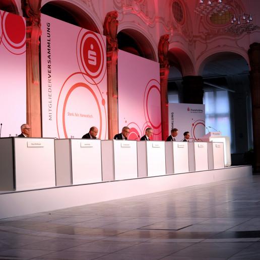 Die Sparkasse Bremen Mitgliederversammlung: Blick auf das Podium auf dem sieben Personen sitzen, jeder Corona Konform mit 1.5 Meter Abstand.