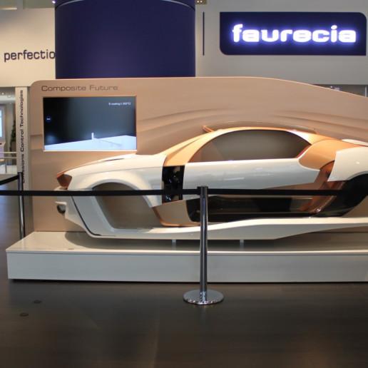 Faurecia Messe: Auf dem Messestand steht eine abgetrennte Karosserie auf einem Podest, davor steht ein Monitor auf dem Informationen zu lesen sind.