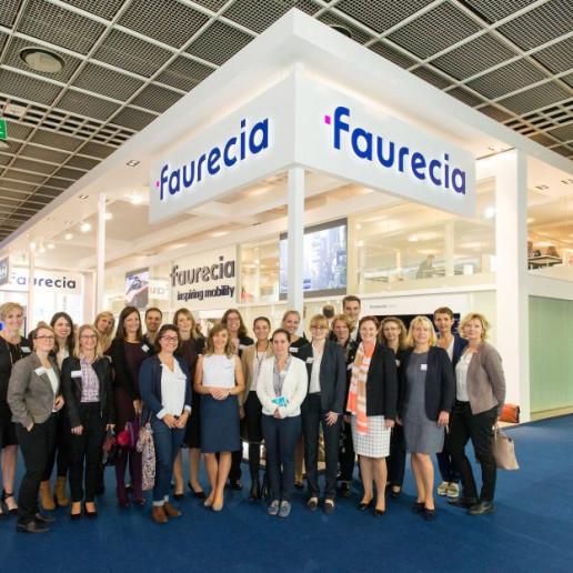 Faurecia Messe: Gruppenbild in der Messehalle mit allen Mitarbeitern vor dem Messestand.