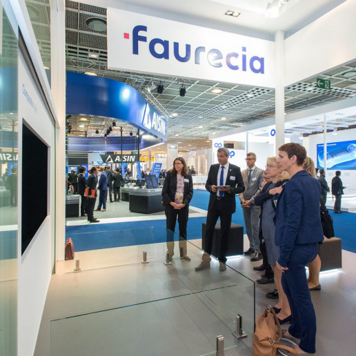 Faurecia Messe: Eine kleine Gruppe Menschen steht vor einem Monitor und schaut sich einen Film an.