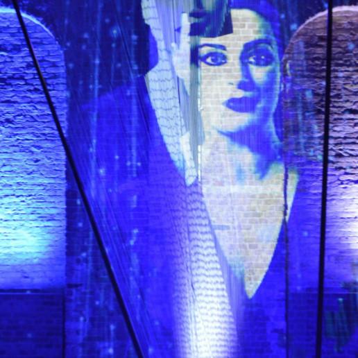 Fraunhofer Jahrestagung: Von der Decke bis auf die Bühne sind Fäden gespannt, auf die Fäden sind Bilder von Frauen projeziert.