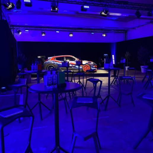 Hyundai Driving Experience: In einem blau beleuchteten Raum stehen Stehtische mit Barhockern und im Hintergrund ein Rennauto auf einem Podest.