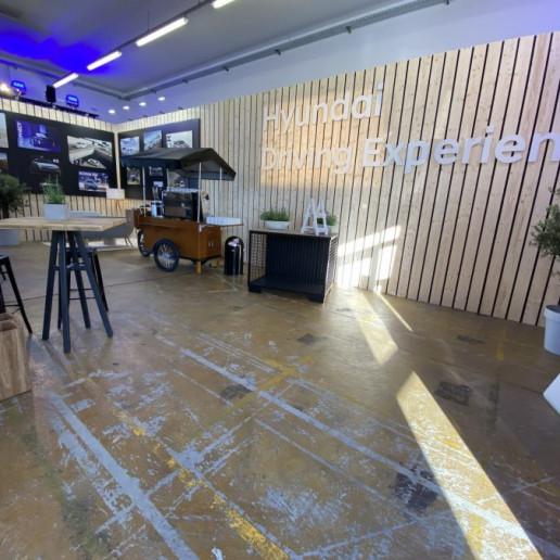 Hyundai Driving Experience: Die Wände des Raumes sind mit Holz verkleidet. Vor der Wand steht ein kleiner Marktstand bei dem es Kaffee und Tee gibt.
