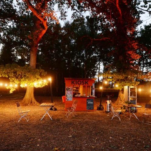 Kaefer Construction 100 Jahre: Ein kleiner Markplatz mitten im Zeltlager. An den Seiten stehen Hängematten in in der Mitte ist ein Kiosk, davor stehen Tische und Stühle.