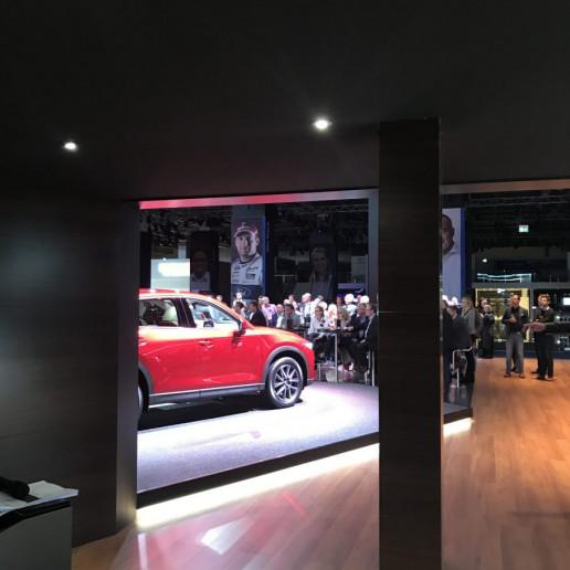 Mazda Messeaktivierung IAA: Blick aus dem Hintergrund auf den Messestand, auf dem ein roter Mazda steht.