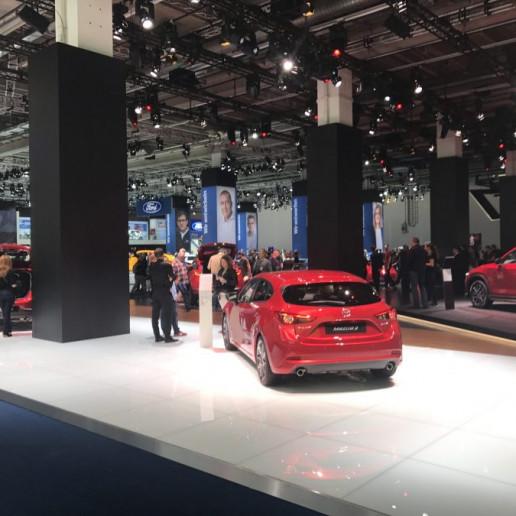 Mazda Messeaktivierung IAA: Heckansicht eines roten Mazda auf dem Messestand.