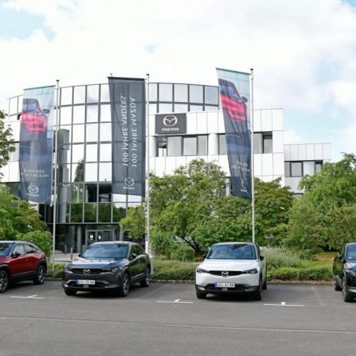 Mazda MX30 Presse Launch: Vier neue Mazda MX30 stehen vor dem Firmengebäude von Mazda.