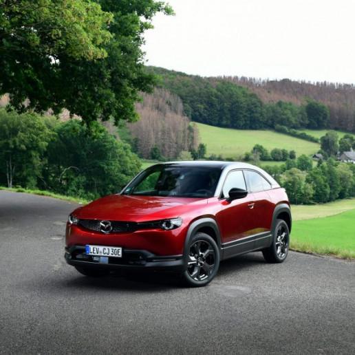 Mazda MX30 Presse Launch: Ein roter Mazda MX30 steht mitten in der Landschaft auf einem Schotterweg, im Hintergrund ist Wald zu sehen.