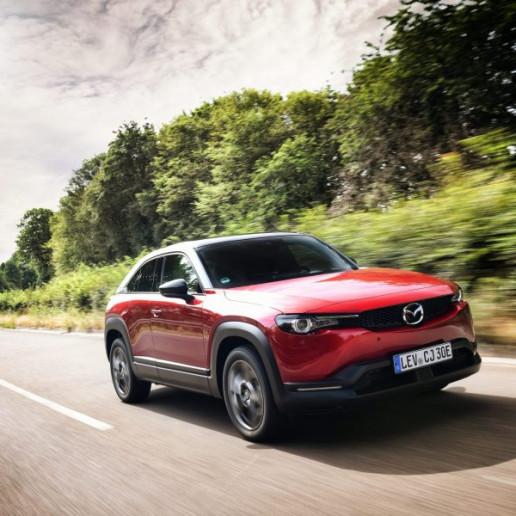 Mazda MX30 Presse Launch: Ein roter Mazda MX30 fährt schnell auf der Strasse durch die Landschaft.