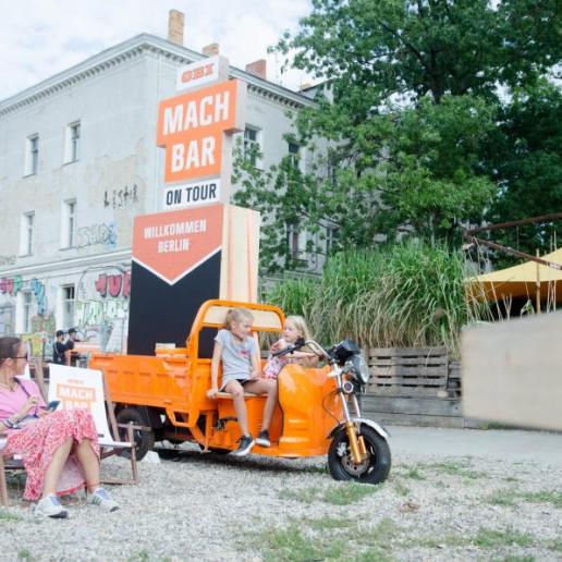 OBI MachBar Roadshow: zwei Kinder sitzen auf einem orangenen Motorrad.