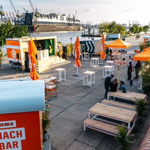OBI MachBar Roadshow: Eventfläche von oben. Hier gibt es Stehtische, Sonnenschirme, und eine kleine Bühne.