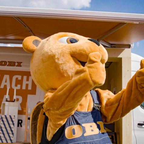 OBI MachBar Roadshow: Das OBI Maskottchen. Es Steht mit beiden Daumen nach oben vor einem OBI Sprinter.