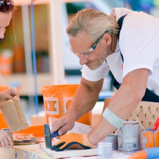 OBI MachBar Roadshow: Ein Obi MachBar Mitarbeiter hilft einer jungen Frau beim zusammenbauen ihres Werkstücks