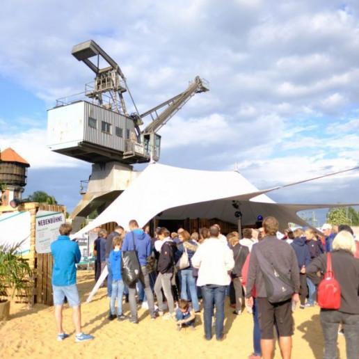 OLB 150 Jahre Festival: Geladene Gäste stehen im Sand vor einem Zelt, im Hintergrund ist ein alter Kran.