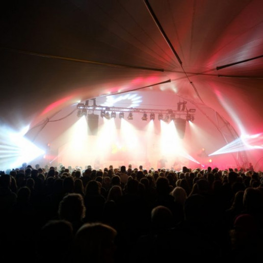 OLB 150 Jahre Festival: Blick in das volle Zelt auf die Bühne. Jede Menge Menschen feiern vor der Bühne, die hell erleuchtet ist.