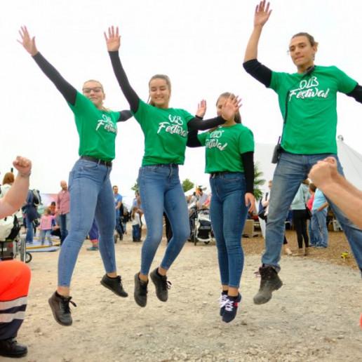 OLB 150 Jahre Festival: Drei junge Frauen und ein junger Mann ,alle im grünen OLB T Shirt, springen in die Luft und heben die Arme dabei.
