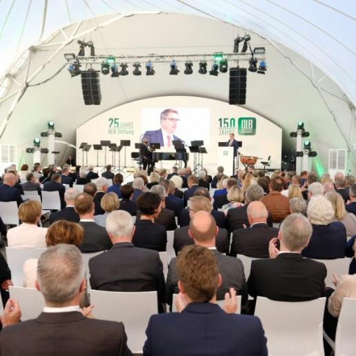 OLB 150 Jahre Festival: Geladene Gäste sitzen im Zelt vor einer Bühne und hören dem Redner zu.