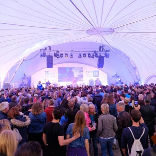 OLB 150 Jahre Festival:Blick von hinten durch das Zelt auf die Bühne.Vor der Bühne stehen jede Mendge Menschen