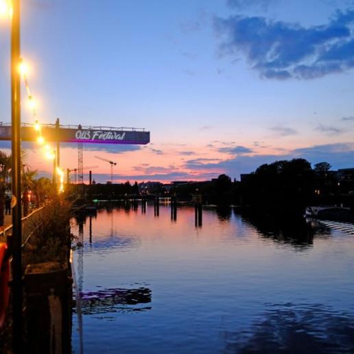 OLB 150 Jahre Festival: Abendlicher Blick über den Fluss Hunte, im Hintergrund steht der große beleuchtete Kran.