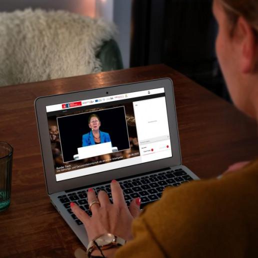 Nahrungs- und Genussmittelwirtschaft: Blick über die Schulter einer Onlineteilnehmerin die vor ihrem Laptop sitzt. Im Livestream ist eine Rednerin zu sehen.