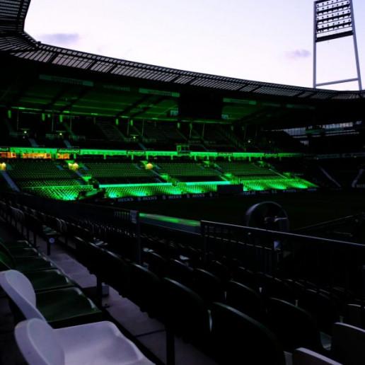 Werder Opening Weekend: Blick in leere wohninvest Weserstadion. Die Westkurve ist grün beleuchtet.